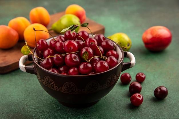 Widok z boku wiśni w misce i wzór gruszki morele na deska do krojenia z brzoskwinią na zielonym tle