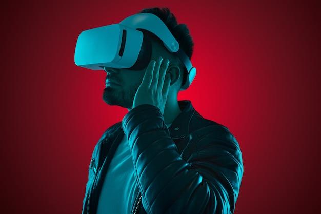 Widok z boku współczesnego brodatego faceta w skórzanej kurtce i goglach vr dostosowujących słuchawki tws podczas oglądania wideo w studio z neonami