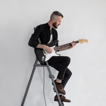 Widok z boku wykonawcy płci męskiej grającej na gitarze elektrycznej na schodach