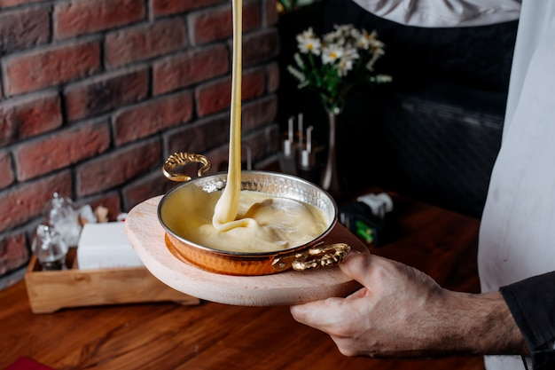 Widok z boku wylewania mieszanki ciasta do formy do pieczenia