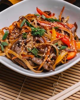 Widok z boku wymieszaj smażony makaron z grillowanym mięsem papryka wiosenna cebula i nasiona sezamu