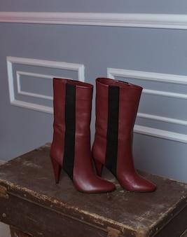 Widok z boku wyściełanego czerwonego buta ze stodoły na walizkach przed szarą ścianą