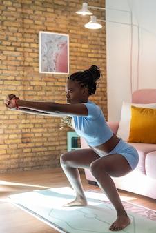 Widok z boku wysportowanego czarnego sportowca wykonującego przysiady stojąc na macie i ćwiczącego podczas treningu w salonie w domu