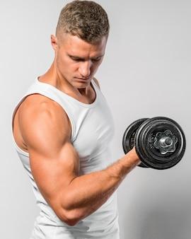 Widok z boku wysportowanego mężczyzny w podkoszulku trenującym z ciężarem