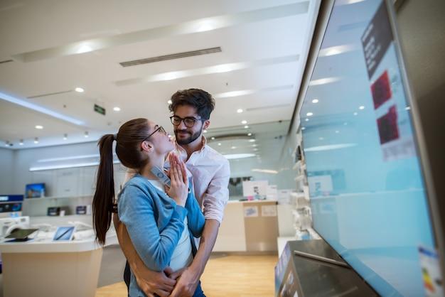 Widok z boku z bliska atrakcyjna szczęśliwa podekscytowana hipster młoda para zakochanych stojących przytulona przed dużym smart tv, podczas gdy dziewczyna modli się do swojego chłopaka w sklepie technicznym.