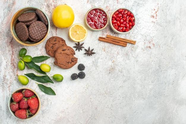 Widok z boku z bliska ciasteczka i jagody ciasteczka truskawki owoce cytrusowe na stole