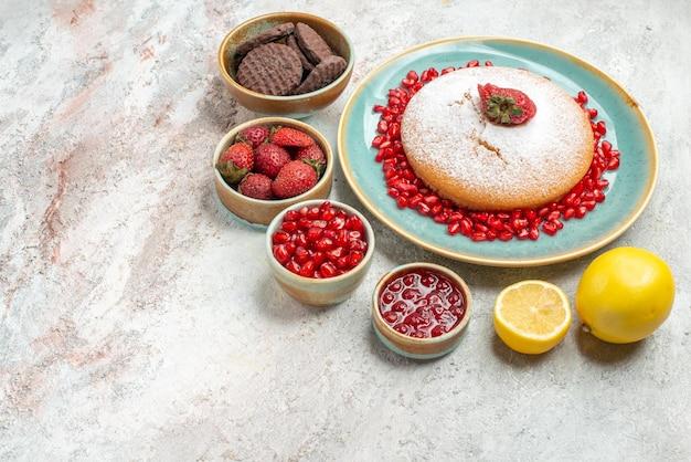 Widok z boku z bliska ciasteczka tort truskawkowy i granatowy miski z jagodami i ciasteczka z owocami cytrusowymi na fioletowym stole