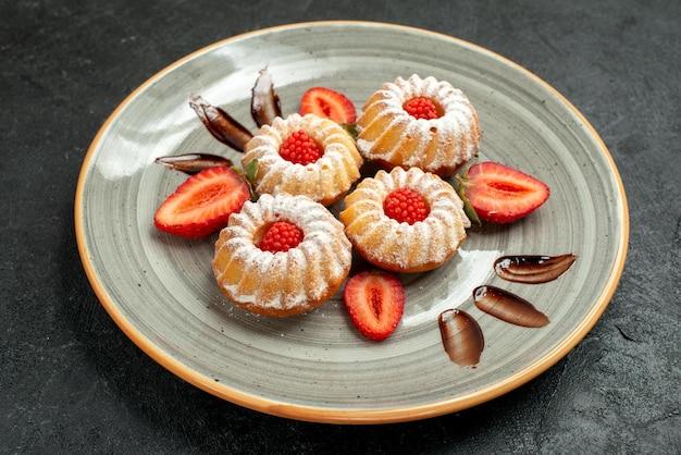 Widok z boku z bliska ciasteczka w talerzowych ciasteczkach z truskawkami i czekoladą na białym talerzu na ciemnym tle