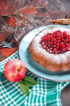 Widok z boku z bliska ciasto ciasto z czerwoną porzeczką jabłko na obrusie widelce cynamon