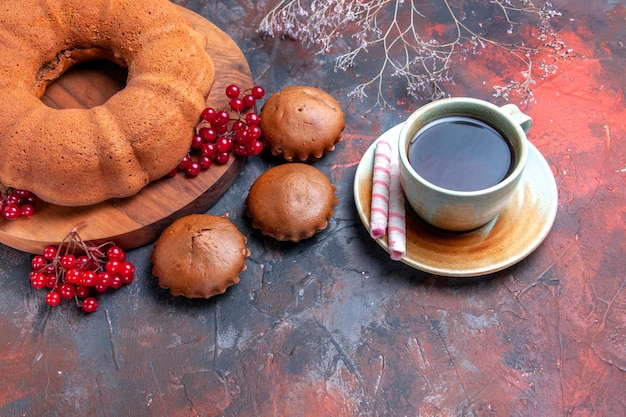 Widok z boku z bliska ciasto ciasto z czerwonymi porzeczkami na desce babeczki filiżanka herbaty z cukierkami