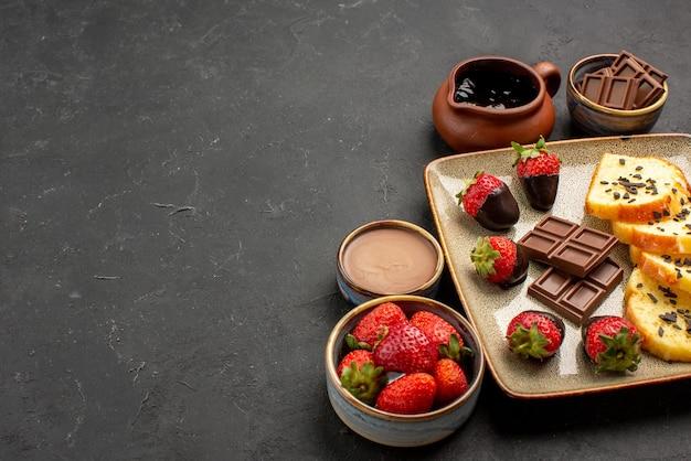 Widok z boku z bliska ciasto deserowe z truskawkami w czekoladzie i czekoladą z miskami kremu czekoladowego i jagodami po prawej stronie ciemnego stołu