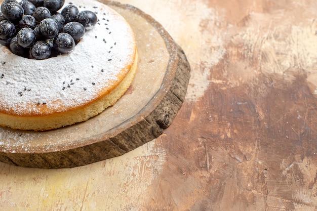 Widok z boku z bliska ciasto na drewnianej desce ciastem z czarnymi winogronami i cukrem pudrem