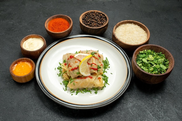 Widok z boku z bliska danie i sosy miski z żółtym sosem ryż kwaśna śmietana czarny pieprz zioła i kolorowe przyprawy wokół białego talerza gołąbki na czarnym stole