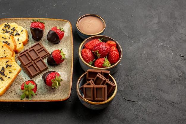 Widok z boku z bliska deser apetyczny tort z truskawkami i czekoladą na szarym talerzu obok misek z truskawkami i kremem czekoladowym na ciemnym tle