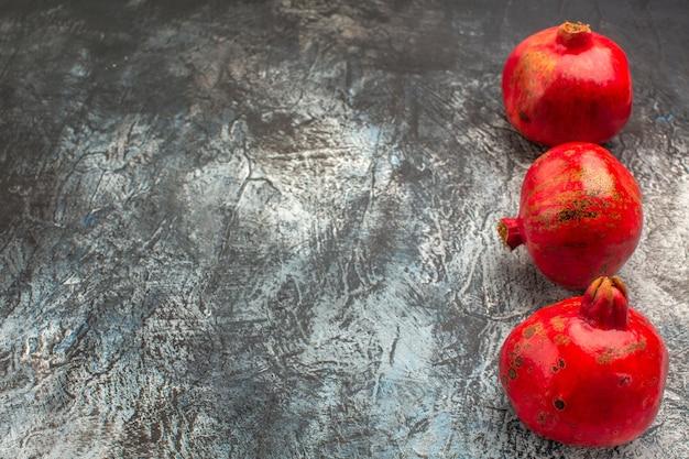 Widok z boku z bliska dojrzałe granaty dojrzałe czerwone granaty na stole