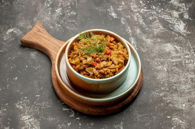 Widok z boku z bliska fasolka szparagowa miska zielonej fasoli z pomidorami i ziołami na płycie kuchennej na czarnej powierzchni