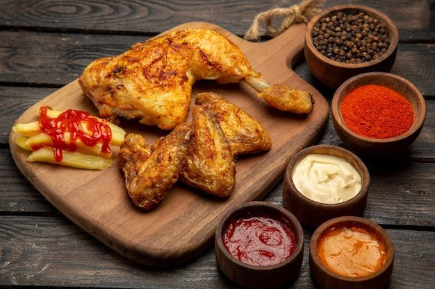 Widok z boku z bliska fastfood frytki i kurczak na desce do krojenia obok ketchupowych sosów z czarnego pieprzu i przypraw na stole
