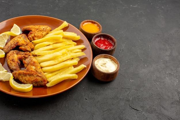 Widok z boku z bliska fastfood pomarańczowy talerz skrzydełek z kurczaka apetyczne frytki i cytryna oraz trzy miski różnych rodzajów sosów na ciemnym stole