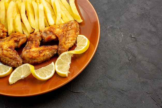 Widok z boku z bliska fastfood pomarańczowy talerz z apetycznymi skrzydełkami z kurczaka frytkami i cytryną na ciemnym tle