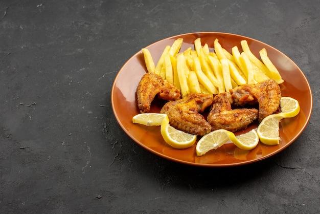 Widok z boku z bliska fastfood talerz smacznych skrzydełek z kurczaka frytki i cytryna na ciemnym tle