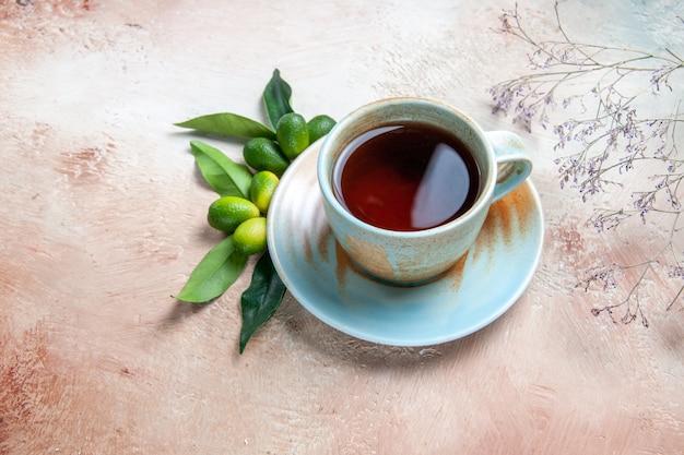 Widok z boku z bliska filiżankę herbaty filiżankę herbaty na owoce cytrusowe spodek