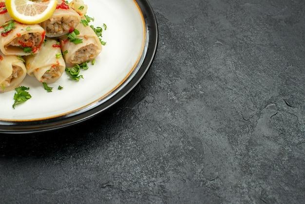 Widok z boku z bliska gołąbka faszerowana kapusta z ziołami cytryna i sos na talerzu po lewej stronie czarnego stołu