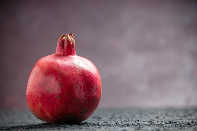 Widok z boku z bliska granat czerwony granat na szarym stole na fioletowym tle