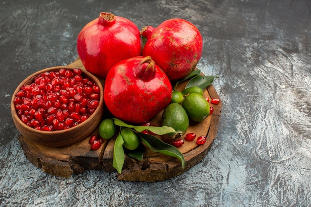 Widok z boku z bliska granaty apetyczny czerwony granat z liśćmi na drewnianej desce do krojenia
