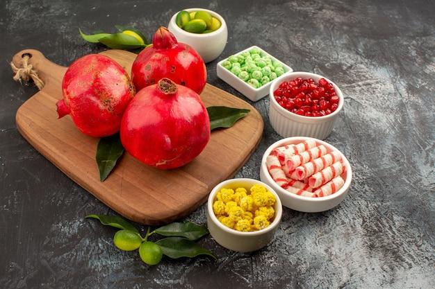 Widok z boku z bliska granaty granaty na desce do krojenia kolorowe cukierki owoce cytrusowe