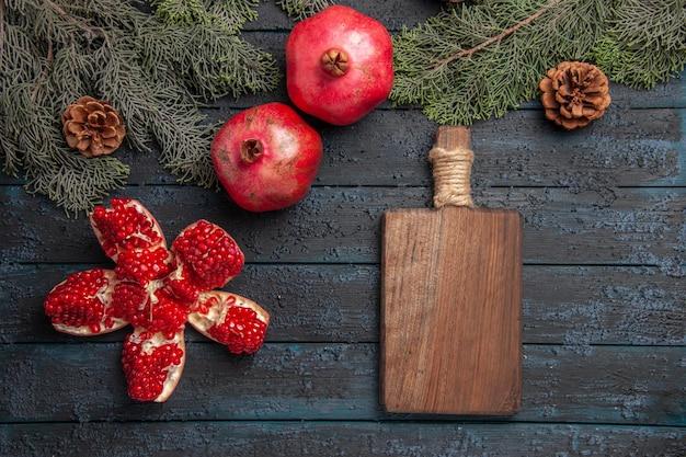 Widok z boku z bliska granaty na stole zgrane granaty obok dwóch czerwonych granatów drewniana deska i świerkowe gałęzie z szyszkami