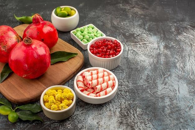 Widok z boku z bliska granaty słodycze owoce cytrusowe w miskach granaty na desce do krojenia