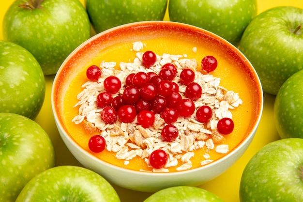 Widok z boku z bliska jabłka apetyczne jabłka wokół miski płatków owsianych czerwonych porzeczek na stole