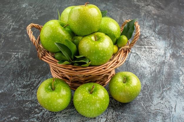 Widok z boku z bliska jabłka zielone jabłka z liśćmi owoców cytrusowych w koszyku