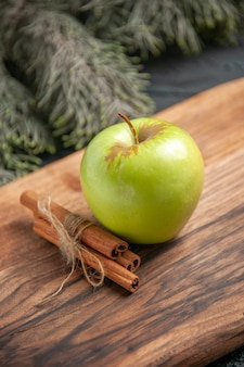 Widok z boku z bliska jabłko i laska cynamonu apetyczne zielone jabłko i laska cynamonu na drewnianej desce