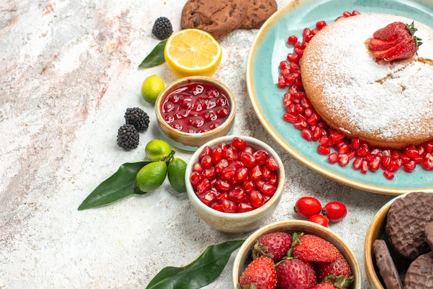 Widok z boku z bliska jagody dżem cytrynowy granat ciasto z truskawkami czekoladowe ciasteczka
