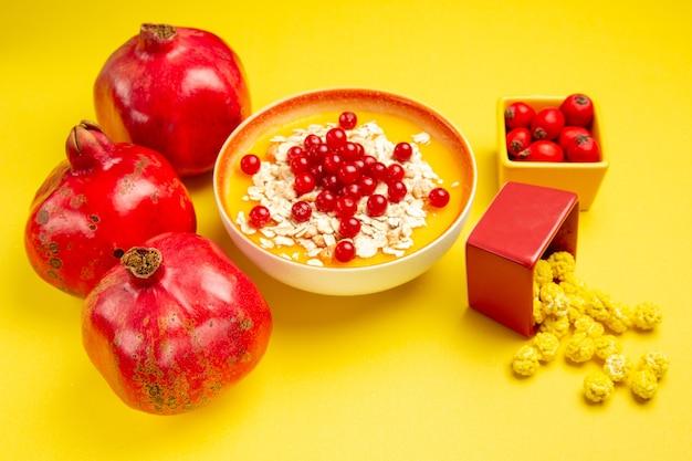 Widok z boku z bliska jagody granaty żółte cukierki kolorowe jagody w miskach