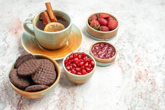 Widok z boku z bliska jagody i herbata filiżanka herbaty z ciasteczkami z dżemem z cytryną i cynamonem