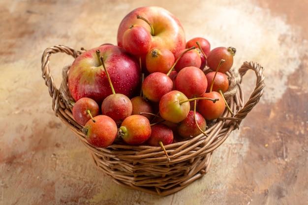 Widok z boku z bliska jagody jagody jabłka w drewnianym koszu na kremowym stole