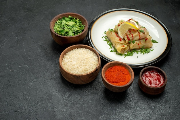 Widok z boku z bliska jedzenie na białym talerzu nadziewanej kapusty z cytryną, ziołami i sosem oraz miski przypraw, ziół ryżowych i sosu na ciemnym tle