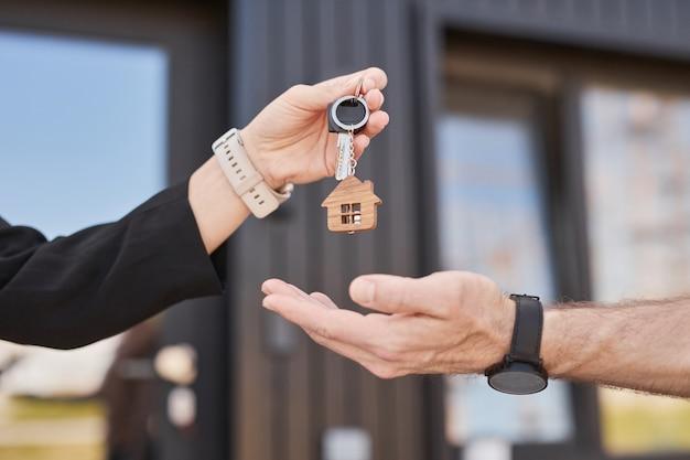 Widok z boku z bliska kobiecego agenta nieruchomości dającego klucze klientowi na zewnątrz, kopia przestrzeń