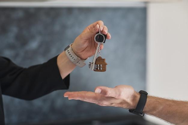 Widok z boku z bliska kobiecego agenta nieruchomości dającego klucze młodemu mężczyźnie kupującemu dom, kopia przestrzeń