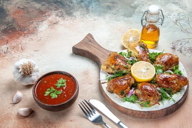 Widok z boku z bliska kurczak kurczak z cytryną zioła czosnek butelka oleju sos widelec nóż