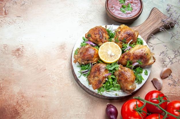 Widok z boku z bliska kurczaka kurczak z ziołami cebulą na pokładzie pomidory sos cebula czosnek