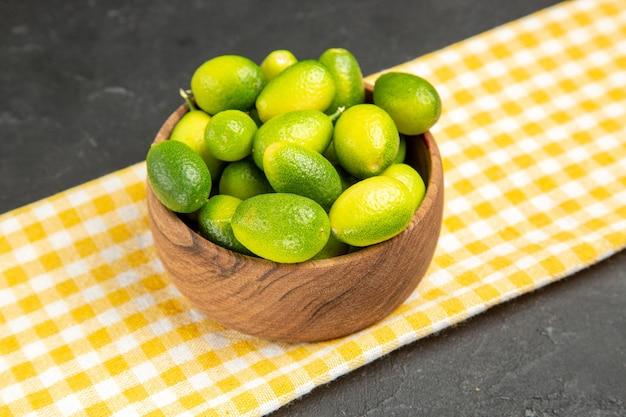 Widok z boku z bliska owoce cytrusowe owoce w misce na obrusie w kratkę