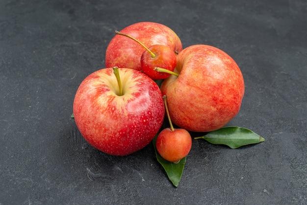 Widok z boku z bliska owoce czerwono-żółte jabłka i jagody z liśćmi