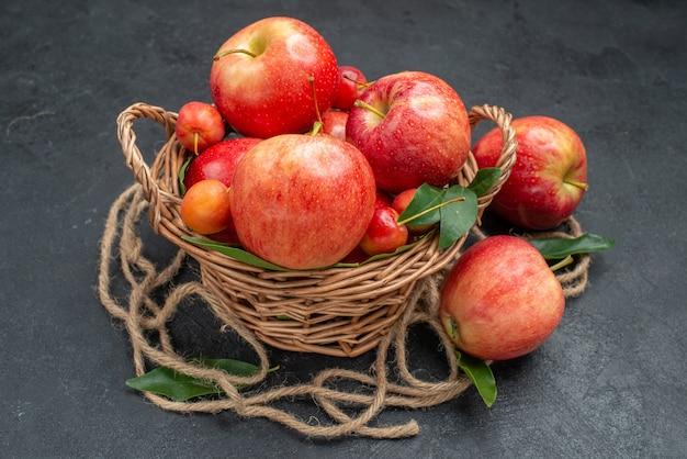 Widok z boku z bliska owoce drewniany kosz apetyczny wiśnie i jabłka z liśćmi
