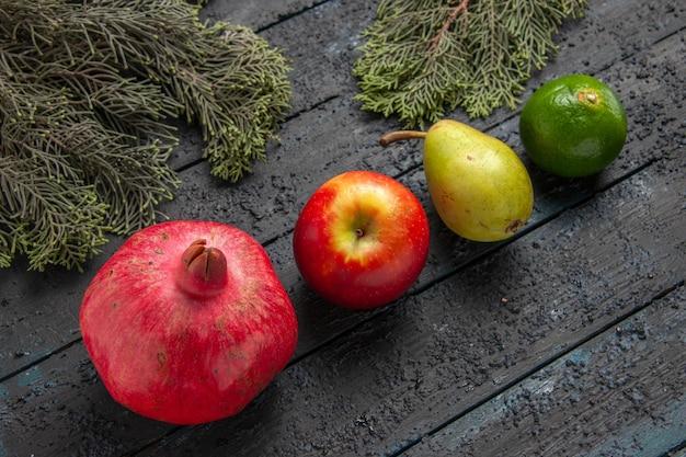Widok z boku z bliska owoce i gałęzie granat jabłko żółta gruszka limonka obok świerkowych gałęzi