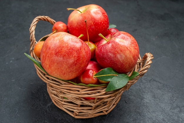 Widok z boku z bliska owoce jabłka i wiśnie z liśćmi w koszu na ciemnym stole