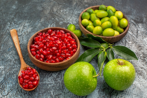 Widok z boku z bliska owoce nasiona granatu łyżka jabłka owoce cytrusowe w misce
