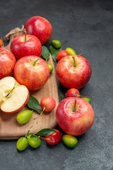 Widok z boku z bliska owoce owoce jagody z liśćmi na planszy obok owoców cytrusowych